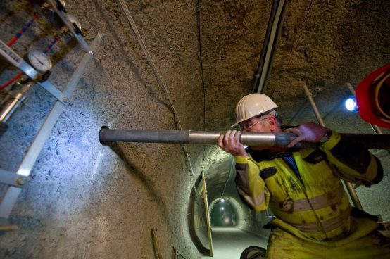 In a gallery of the Mont Terri rock laboratory a researcher inserts a packer system into a horizontal borehole.