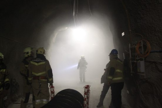 In the foreground, three firefighters in the rock laboratory; in the centre, a firefighter with a powerful flashlight in the smoke-filled tunnel. The smoke has been artificially created for this exercise.